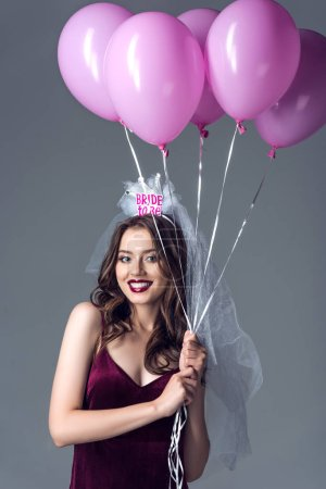 smiling future bride in veil for bachelorette party holding bunch of pink air balloons isolated on grey