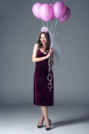 happy future bride in veil for bachelorette party holding bunch of pink air balloons on grey