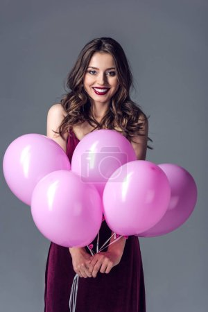 smiling young woman with bunch of pink balloons isolated on grey
