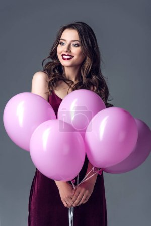 happy young woman with bunch of pink balloons isolated on grey
