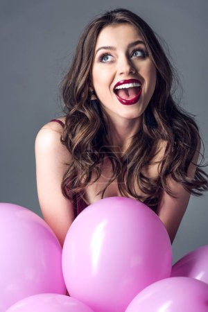 excited young woman with bunch of pink balloons isolated on grey