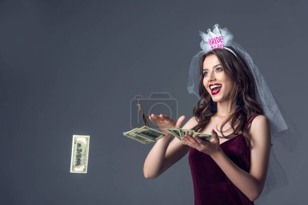 beautiful future bride in veil for bachelorette party throwing money away isolated on grey