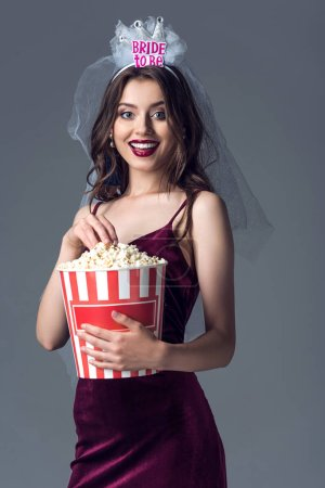 happy future bride in veil for bachelorette party isolated with popcorn bucket on grey