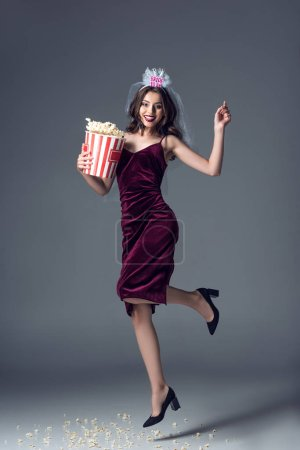 beautiful future bride in veil for bachelorette party jumping with bucket of popcorn on grey