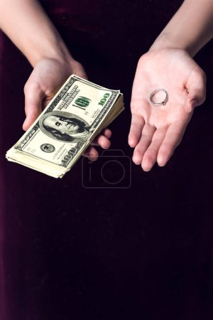 cropped shot of woman holding cash and wedding ring, marriage of convenience concept