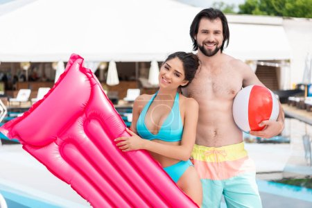 couple swimsuits posing with inflatable mattress and ball near swimming pool