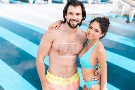 smiling couple hugging near swimming pool