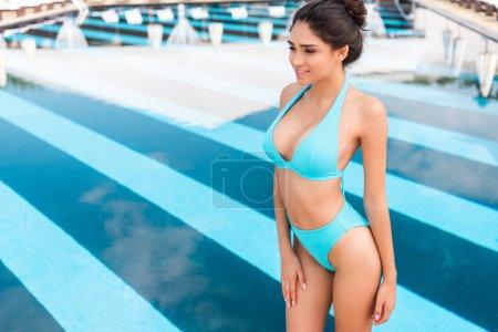 beautiful slim girl posing in blue bikini near swimming pool