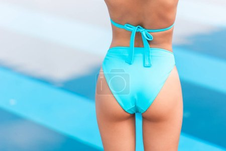 Photo for Cropped back view of tanned female butt in blue bikini - Royalty Free Image