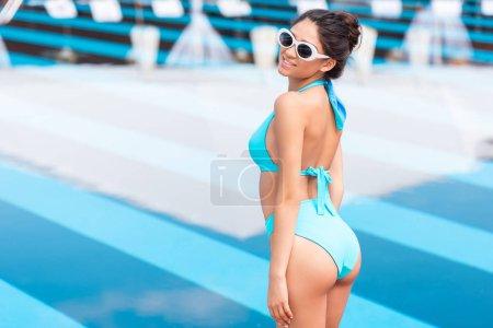 attractive tanned girl posing in blue bikini near swimming pool