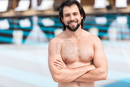 bearded man standing with crossed arms at swimming pool