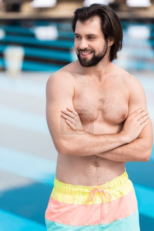 handsome cheerful man posing with crossed arms at swimming pool