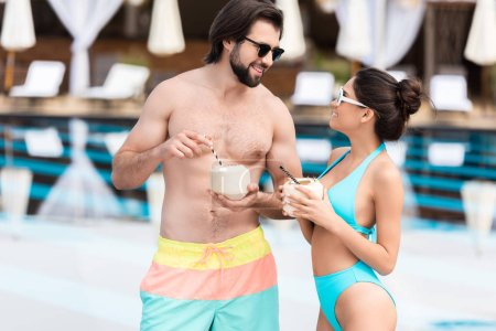 young couple in sunglasses with coconut cocktails standing near swimming pool