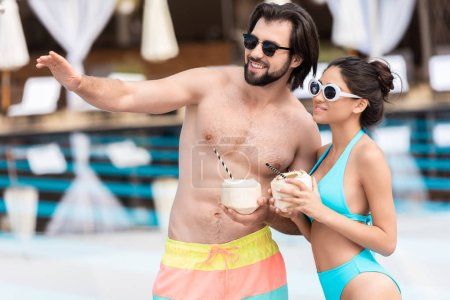 Photo for Young couple in sunglasses with coconut cocktails, man showing something - Royalty Free Image