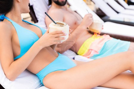 cropped view of couple relaxing on sunbeds with coconut cocktails