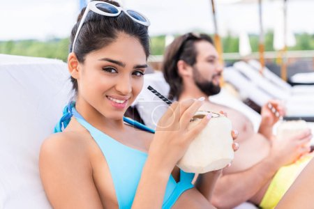 young couple relaxing on sunbeds with fresh coconut cocktails, selective focus