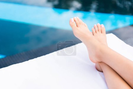 Photo for Partial view of female feet lying on sunbed at poolside - Royalty Free Image