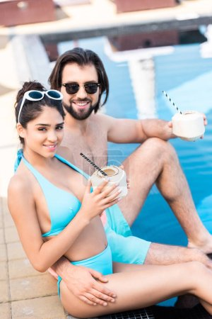 young couple in sunglasses with coconut cocktails relaxing at swimming pool