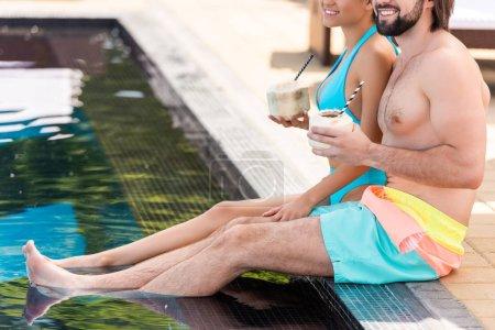 recadrée vue du couple se détendre près de la piscine avec des cocktails de noix de coco