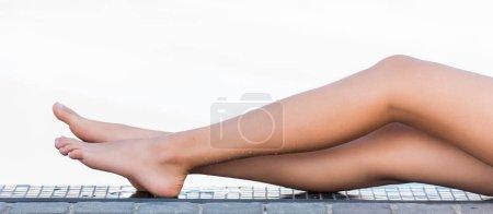 partial view of tanned female legs having sunbath