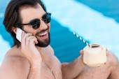 smiling man with coconut cocktail talking on smartphone at poolside