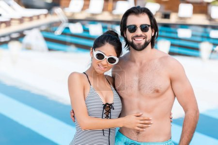 beautiful couple in sunglasses embracing near swimming pool