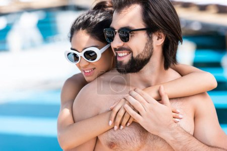 smiling couple in sunglasses embracing near swimming pool