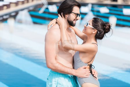 young couple in sunglasses embracing near swimming pool