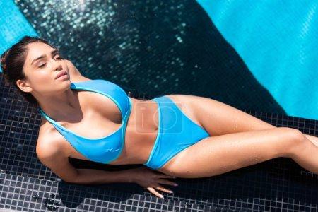 top view of beautiful woman in bikini sunbathing at swimming pool