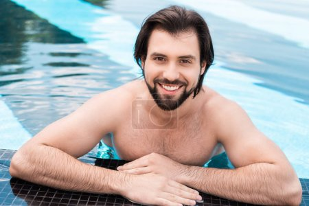bearded smiling man in swimming pool looking at camera