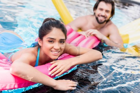 happy couple swimming on yellow and pink inflatable mattress in pool