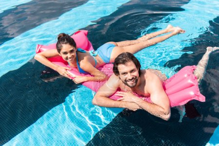 cheerful couple swimming on pink inflatable mattress in pool