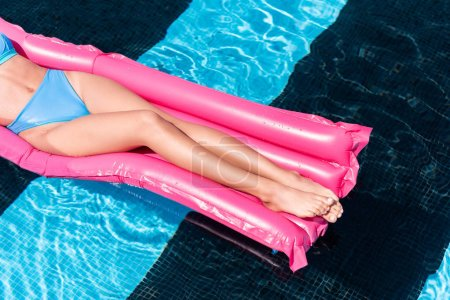low section view of girl resting on pink inflatable mattress in swimming pool
