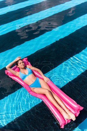 attractive girl in bikini relaxing on inflatable mattress in swimming pool