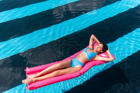 young woman in bikini lying on pink inflatable mattress in swimming pool