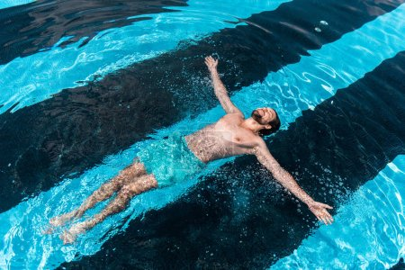 bearded man floating in swimming pool