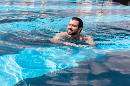 smiling bearded man swimming in pool