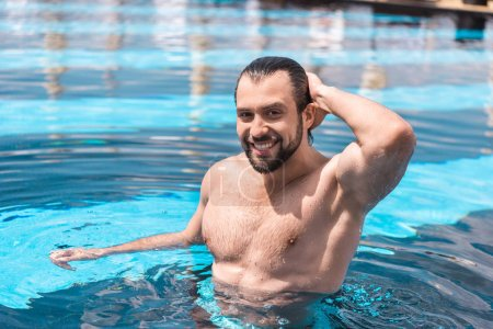 smiling bearded man standing in swimming pool