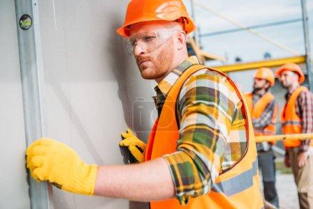 Photo pour Générateur de concentré à l'aide de niveau à bulle sur le chantier, tandis que ses collègues debout sur le fond - image libre de droit