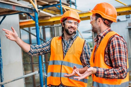 Photo for Happy builders in reflective vest and hard hat pointing at building house - Royalty Free Image