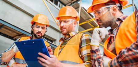 Photo for Wide shot of group of builders in hard hats and reflective vests looking at clipboard - Royalty Free Image