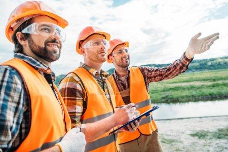 Photo pour Groupe de constructeurs en casquettes et gilets réfléchissants pointant quelque part - image libre de droit