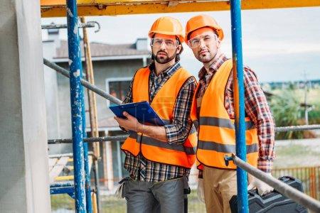 Photo pour Beaux constructeurs confiants avec presse-papiers debout sur le chantier de construction - image libre de droit