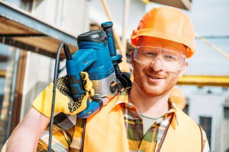 handsome smiling builder holding power drill on shoulder and looking at camera