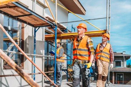 Foto de Grupo de constructores guapos trabajando juntos en el sitio de construcción - Imagen libre de derechos