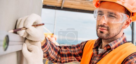 wide shot of handsome builder using bubble level at construction site