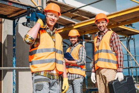 Photo for Group of smiling builders with building equipment standing at construction site and looking at camera - Royalty Free Image