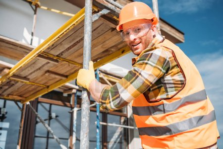 handsome builder climbing on scaffolding at construction site and looking at camera