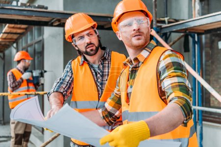 handsome thoughtful builders with blueprint looking away