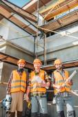 Groupe de sourire équipé constructeurs en regardant la caméra sur le chantier